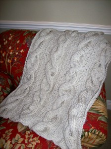 Knitted throw with cables