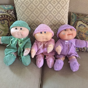 Originally knitted for triplets Ivy, Rose and Violet, Carole's beautiful creations now adorn the girls' collectible dolls.